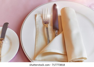 Served table in restaurant, close-up, pink tablecloth