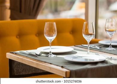 Served table in restaurant. Glasses, fork, knife served for dinner in restaurant with cozy interior.
