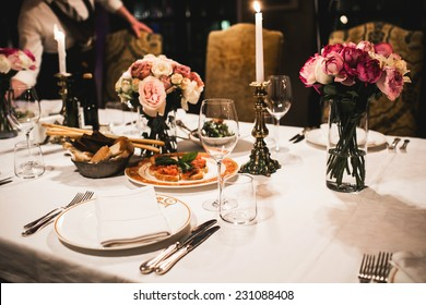 Served table set with flowers and empty wine glasses in french restaurant