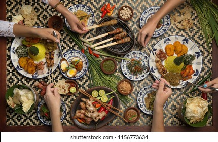 Served table top view, dinner. People eat food together. Top view of food dishes and hands