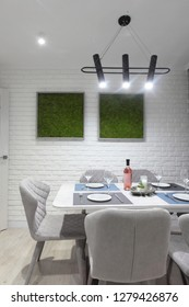 Served table with white plates glasses and bottle of wine. White kitchen interior with grey chairs and and moss on the wall in new luxury home with lights on.