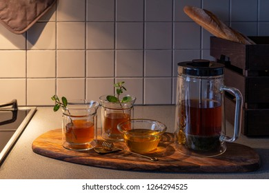 Served tea with a sprigs of mint and honey on a wooden board