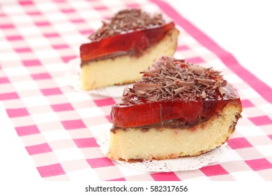 served two slices of delicious cherry cheese cake with cherry topping and decorated with chocolate on checkered tablecloth