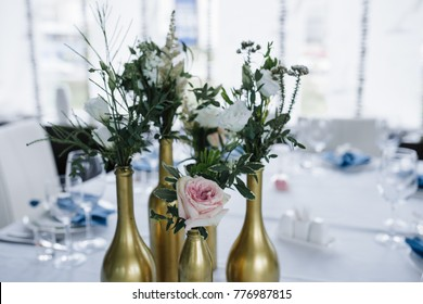 Served for wedding banquet table in blue white. Wedding decoration. Blue napkin with flower on a white plate. Golden bottles are vases for flowers.