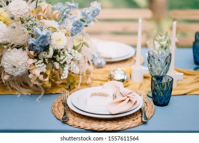 Served wedding plate on reception table decorated by blue tablecloth. Bouquet of ranunculuses on background. Decor