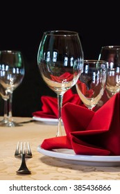 Served white plate with fork and wine glasses. red napkin. black background, soft focus
