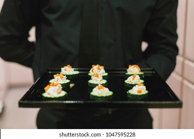Server dressed in black presents tray of healthy appetizers