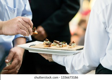 a server holding a tray full of snacks during a catered event
