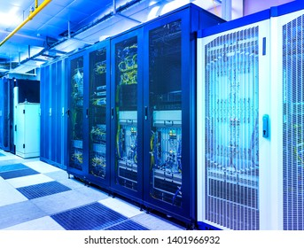 Server room with control modules in racks datacenter under blue toning