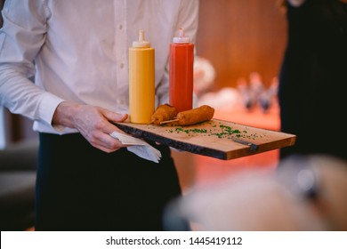 Server in white dress shirt and black pants carrying corn dogs on a live edge cutting board with ketchup and mustard in plastic dispenser bottles