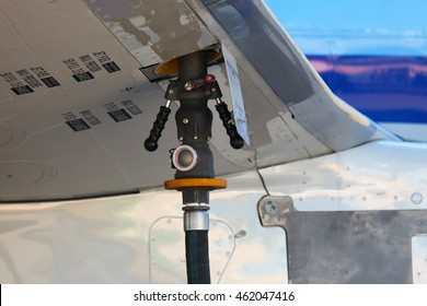 Service airplane before departure. The process of refueling. Fuel hose inserted in the aircraft wing.