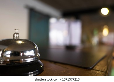 Service bell locating at reception. Silver call bell on table, receptionists on background.