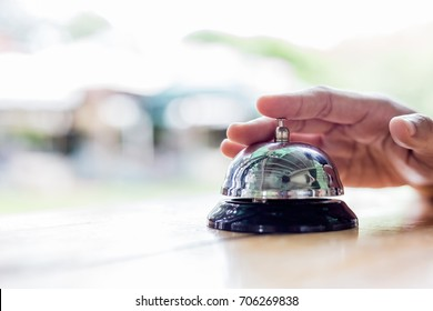 Service Bell. Person using their finger to ring a counter bell.Hotel service bell on a table white glass and simulation hotel background. Concept hotel, travel, room service for hotel business.