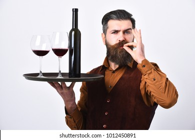 Service and catering concept. Barman with serious face holds italian drink showing perfect taste sign. Man with beard holds alcohol on white background. Waiter with tray, bottle and glass of red wine