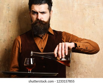 Service and catering concept. Barman with serious face pours scotch or brandy from bulb to glass. Waiter with glass and bottle of whiskey on tray. Man with beard holds cognac on beige wall background.