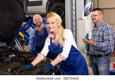 Service crew and cheerful client standing near car