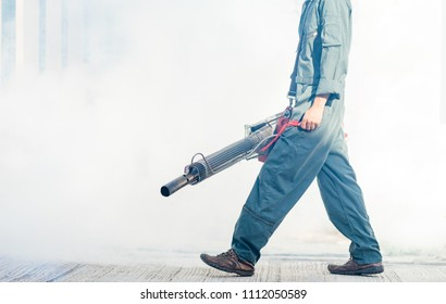Service Employee pest control man in uniform trying killing insects and fogging to eliminate mosquito for preventing spread dengue fever and zika virus.Worker fogging residential area with chemical.