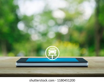 Service fix car with wrench tool flat con on modern smart mobile phone screen on wooden table over blur green tree in park, Business repair car service online concept