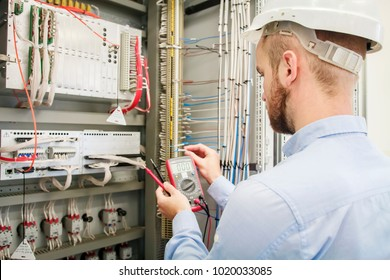 Service man with multimeter in hands adjusts electric control panel. Engineer in helmet tests device of protection. Worker checks electrical industrial equipment. Engineering work in automation box