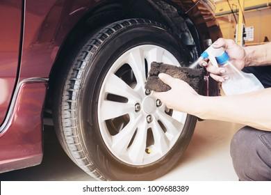 Service man is waxing car tire garage - car maintenance service concept