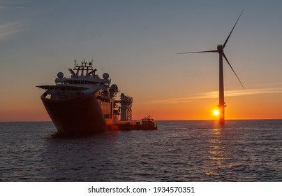 Service operational vessel, with crew transfer vessel alongside and sun setting on wind turbine - Shutterstock ID 1934570351