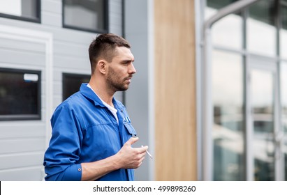 service, repair, maintenance and people concept - auto mechanic smoking cigarette at car shop or garage outdoors