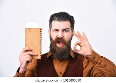 Service and restaurant catering concept. Man with beard and mustache holds bill on white background. Waiter with check book shows ok sign. Barman with satisfied face brings order or change.