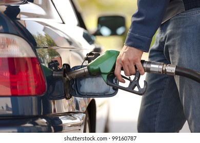 Service station worker filling up car with fuel, close-up
