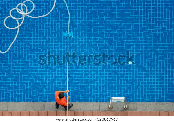 Service and technology. Top view of man cleaning swimming pool with vacuum robot.