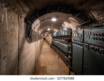 Service tunnel of an old abandoned miltary bunker. Electrical installations, cables and control panels.