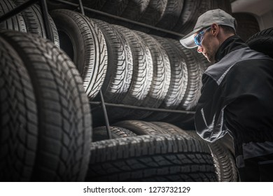 Service Worker with Power Tool Between Tires. Automotive Industry. Car Tires Sales and Repair. Vulcanizing Service.