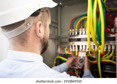 Serviceman adjusts fuse box. Electrician engineer measures voltage in power electrical cabinet.