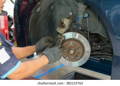 Serviceman checking brake system in a car at garage