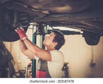 Serviceman checking suspension in a car workshop