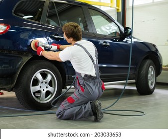 Serviceman polishing car body with machine  in a workshop