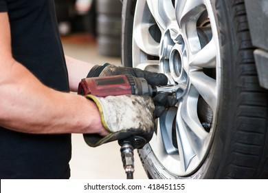 serviceman removing bolt from a wheel  using pneumatic gun, tire replacement