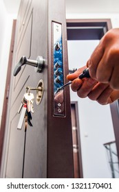 Serviceman is repairing the door lock with screwdriver