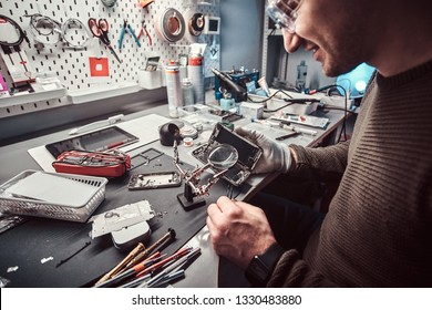 Serviceman uses magnifier and tweezers to repair damaged smartphone in the electronic workshop.