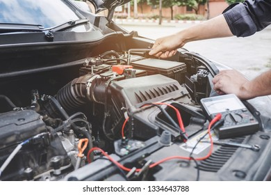 Services car engine machine concept, Automobile mechanic repairman hands repairing a car engine automotive workshop with a wrench and digital multimeter testing battery, car service and maintenance.