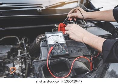 Services car engine machine concept, Automobile mechanic repairman hands checking a car engine automotive workshop with digital multimeter testing battery, car service and maintenance.