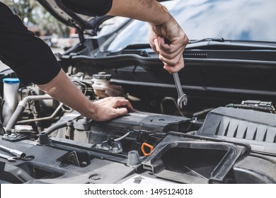 Services car engine machine concept, Automobile mechanic repairman hands repairing a car engine automotive workshop with a wrench, car service and maintenance.