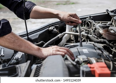 Services car engine machine concept, Automobile mechanic repairman hands repairing a car engine automotive workshop with a wrench, car service and maintenance.