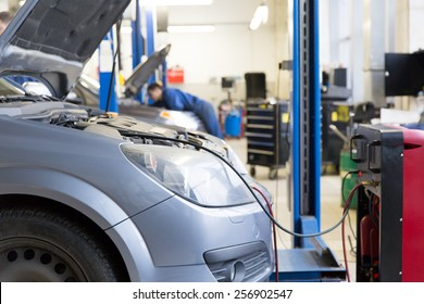 Servicing car air conditioner in auto repair shop
