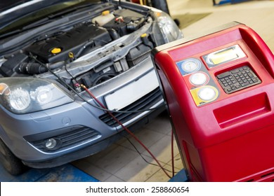 Servicing car air conditioner in vehicle service or repair workshop