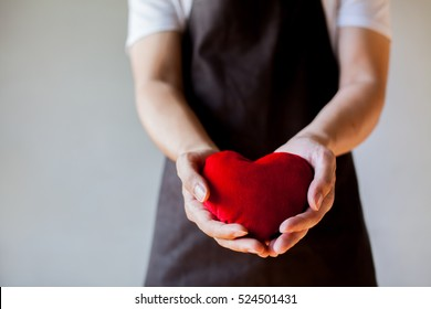 Servicing man in apron holding heart - customer relationship and service minded business concept