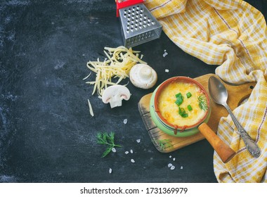 serving baked julienne with mushrooms, onions and cheese on black table, on wooden board, plaid towel, cheese grater, top view