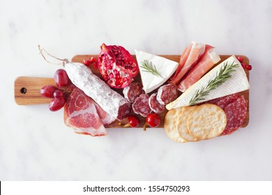 Serving board of assorted meats, cheeses and appetizers. Top view on a white marble background.