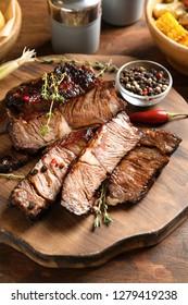 Serving board with delicious barbecued steak and spices on wooden table