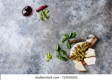 Serving board with sliced camembert cheese and baked bunch of green grapes served with bread, glass of red wine, corkscrew, green leaves, fork over gray texture background. Top view with copy space