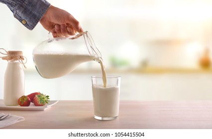 Serving breakfast milk with a jug in a glass on a white wooden kitchen table. Horizontal composition. Front view